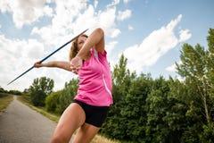 Jeune femme jetant un javelot en nature Photo stock