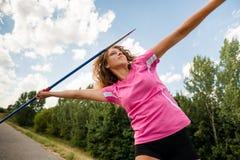 Jeune femme jetant un javelot en nature Photographie stock