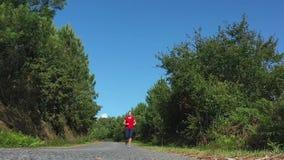 Jeune femme jogging sur la route dans la forêt, gros plan banque de vidéos