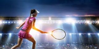Jeune femme jouant au tennis dans l'action Media m?lang? image stock