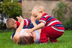Jeune femme jouant avec des enfants à l'extérieur Photo libre de droits
