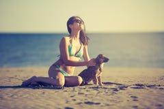 Jeune femme jouant avec l'animal familier de chien sur la plage pendant le lever de soleil ou le coucher du soleil Fille et chien Image libre de droits