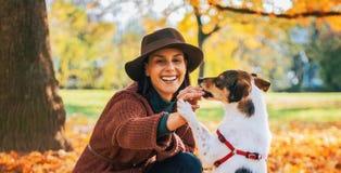 Jeune femme jouant avec le chien dehors en automne image stock