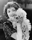 Jeune femme jouant avec son chien et sourire (toutes les personnes représentées ne sont pas plus long vivantes et aucun domaine n Photo libre de droits