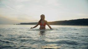 Jeune femme jouant dans l'océan au coucher du soleil d'or rêveur banque de vidéos