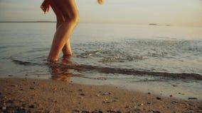 Jeune femme jouant dans l'océan au coucher du soleil d'or rêveur clips vidéos