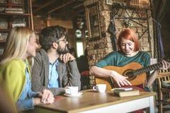 Jeune femme jouant la guitare à ses amis au café Images libres de droits