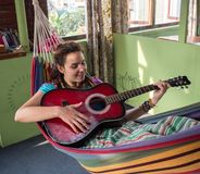Jeune femme jouant la guitare Photographie stock