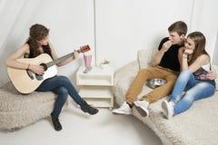 Jeune femme jouant la guitare avec des amis s'asseyant sur le sofa Images stock