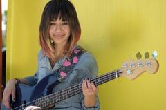 Jeune femme jouant la guitare basse bleue Photographie stock