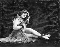 Jeune femme jouant la guitare dans une jupe d'herbe de Hawaïen (toutes les personnes représentées ne sont pas plus long vivantes  images libres de droits