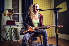 Jeune femme jouant la guitare et le chant eletric Photo libre de droits