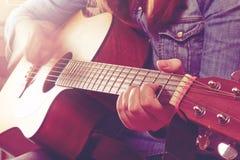 Jeune femme jouant la guitare et tenant la corde de doigts plan rapproché p image stock