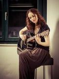 Jeune femme jouant la guitare par la fenêtre Images stock
