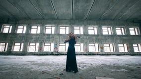 Jeune femme jouant le violon dans une chambre avec le graffiti sur des murs banque de vidéos