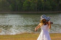 Jeune femme jouant le violon sur le fond de nature Photographie stock libre de droits