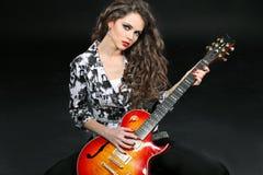 Jeune femme jouant sur la guitare sur le noir Photos libres de droits