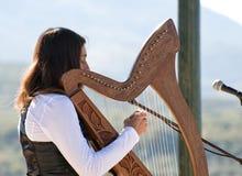 Jeune femme jouant une harpe Photos stock