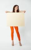 Jeune femme joyeuse dans le pantalon orange tenant la plaquette vide image libre de droits