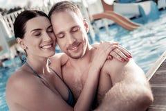 Jeune femme joyeuse et homme appréciant le temps ensemble dans la piscine Photo libre de droits