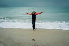 Jeune femme joyeuse se tenant sur une plage et une étendue froides du ` s d'hiver Photographie stock libre de droits