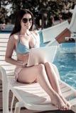 Jeune femme joyeuse souriant tout en travaillant à l'ordinateur portable et à prendre un bain de soleil photographie stock libre de droits