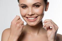 Jeune femme joyeuse tenant le fil dentaire près de la bouche Image stock