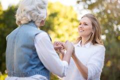 Jeune femme joyeuse tenant ses mains de mère Photo stock