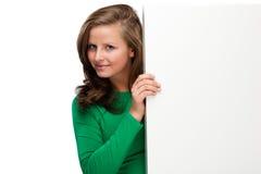 Jeune femme attirante derrière le conseil vide sur le fond blanc Image libre de droits