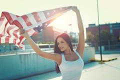 Jeune femme jugeant le drapeau des Etats-Unis aérien dehors Images libres de droits