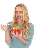 Jeune femme jugeant un bol de choux de bruxelles dégoûté Photo libre de droits