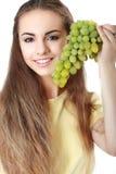 Jeune femme jugeant un groupe de raisins d'isolement Photos libres de droits