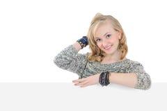 Jeune femme jugeant un panneau-réclame blanc d'isolement Photographie stock libre de droits