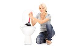 Jeune femme jugeant un plongeur posé par une toilette Photo stock