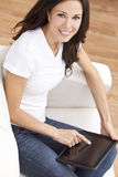 Jeune femme à l'aide de l'ordinateur de tablette à la maison Photos stock