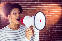 Jeune femme à l'aide de son mégaphone dans la lumière Image stock