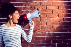 Jeune femme à l'aide de son mégaphone dans la lumière Photo stock