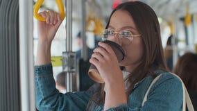 Jeune femme ?l?gante appr?ciant le voyage dans le tram moderne, se tenant avec du caf? dans le transport en commun banque de vidéos