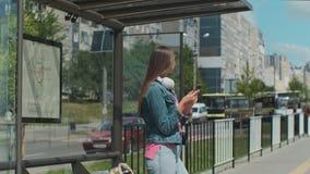 Jeune femme ?l?gante attendant le transport en commun tout en se tenant ? la station moderne de tram dehors clips vidéos