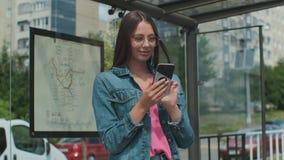 Jeune femme ?l?gante attendant le transport en commun tout en se tenant ? la station moderne de tram dehors banque de vidéos