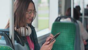 Jeune femme ?l?gante employant le transport en commun, se reposant avec le t?l?phone et les ?couteurs dans le tram moderne banque de vidéos