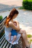 Jeune femme, la mère du nouveau-né, allaitant son bébé l'en public, doucement couvrant et protégeant son enfant contre le soleil images stock