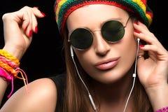 Jeune femme à la mode appréciant la musique par l'écouteur Images libres de droits