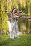 Jeune femme ? la mode jouant le violon en parc La vue d'ensemble image stock