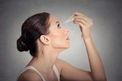Jeune femme latérale de profil appliquant des gouttes pour les yeux Photo stock