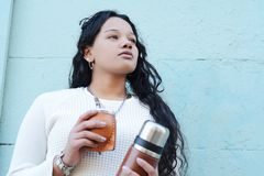 Jeune femme latine buvant du thé traditionnel de compagnon de yerba images stock