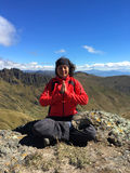 Jeune femme latine s'asseyant faisant le yoga sur un dessus de montagne Photos stock