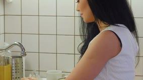 Jeune femme lavant la pomme verte sous l'eau banque de vidéos