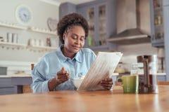 Jeune femme lisant le journal tout en mangeant le petit déjeuner à la maison image stock