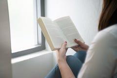 Jeune femme lisant un livre à la maison Image libre de droits